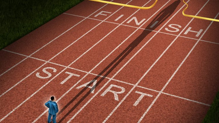 Forward thinking business concept for success acceleration with a businessman standing on the start line in a track and feild path with a cast shadow breaking through the finish line ribbon for victory.